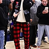 When she sat courtside with friends and sisters Kim and Kourtney at the CIF Open Division Playoffs at Sierra Canyon High School, Kendall showed off her race car love in a patchwork CITGO bomber. She completed her look with red checked pants, black booties, and a colorblock sweater.