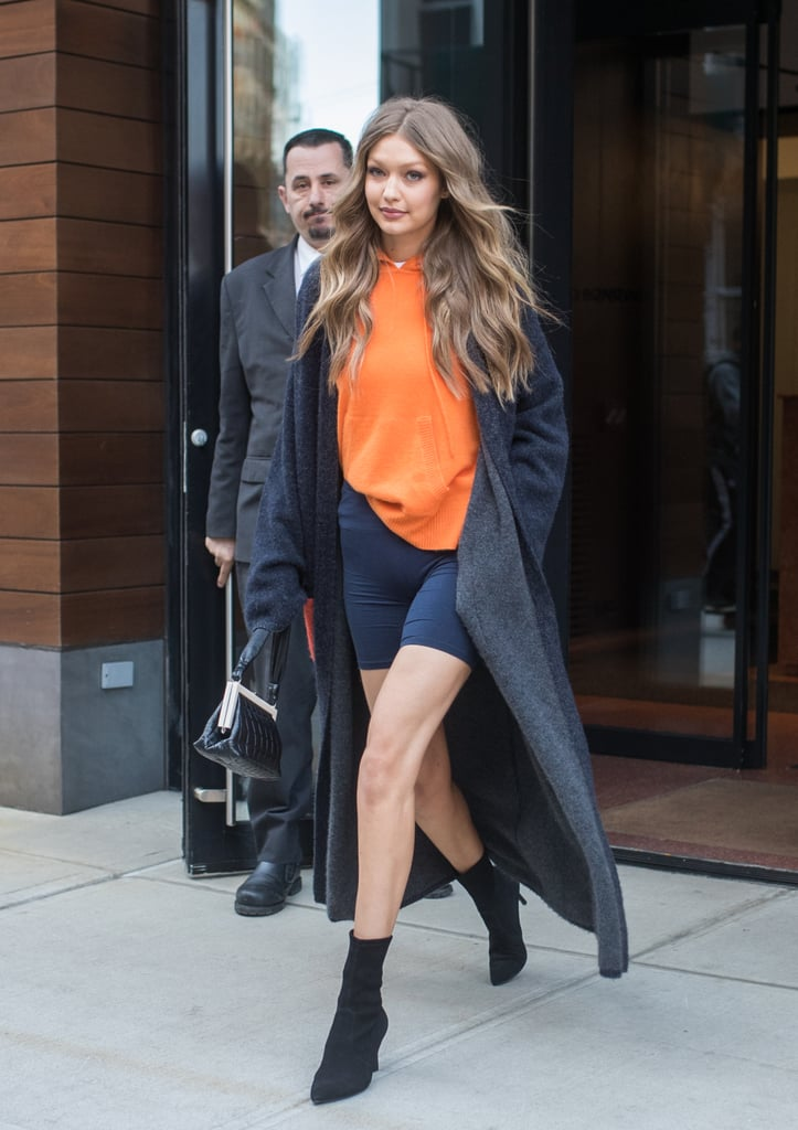 Gigi Hadid styling an orange sweater with a long duster and sock boots.