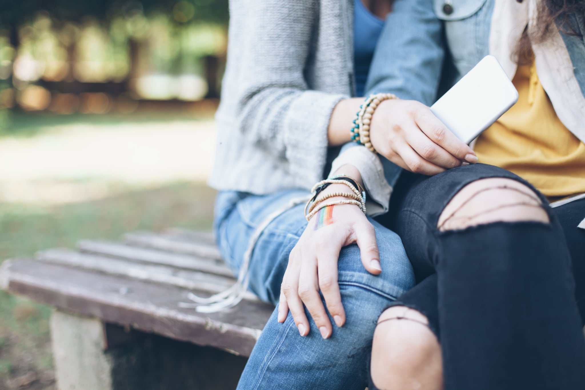 Close up of two unrecognizable women sitting on bench and embracing. One holding smart phone, other with rainbow flag drawned on hand. Both with casual clothes and bracelets.