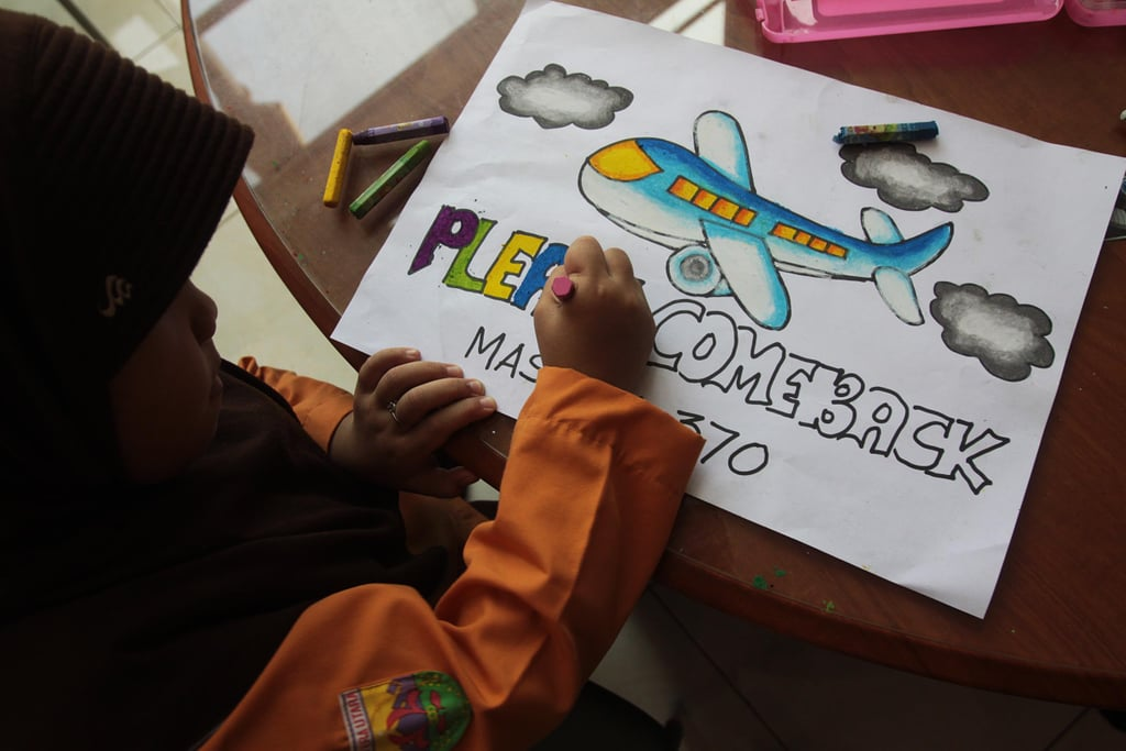 An Indonesian child colored in letters on a poster with a hopeful message on Saturday.