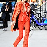 Gigi wore a head-to-toe orange look while walking around NYC in December, pairing a blazer and matching trousers by Ronald van der Kamp. She paired the look with a leather Moschino trench coat and Christian Louboutin ankle boots.