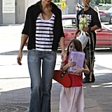 Suri Cruise juggled a doll and a purse as she strolled with Katie Holmes.