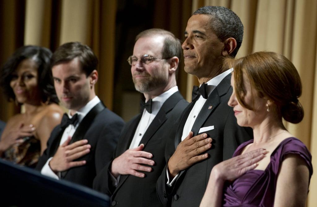 President Obama stood to salute the flag.