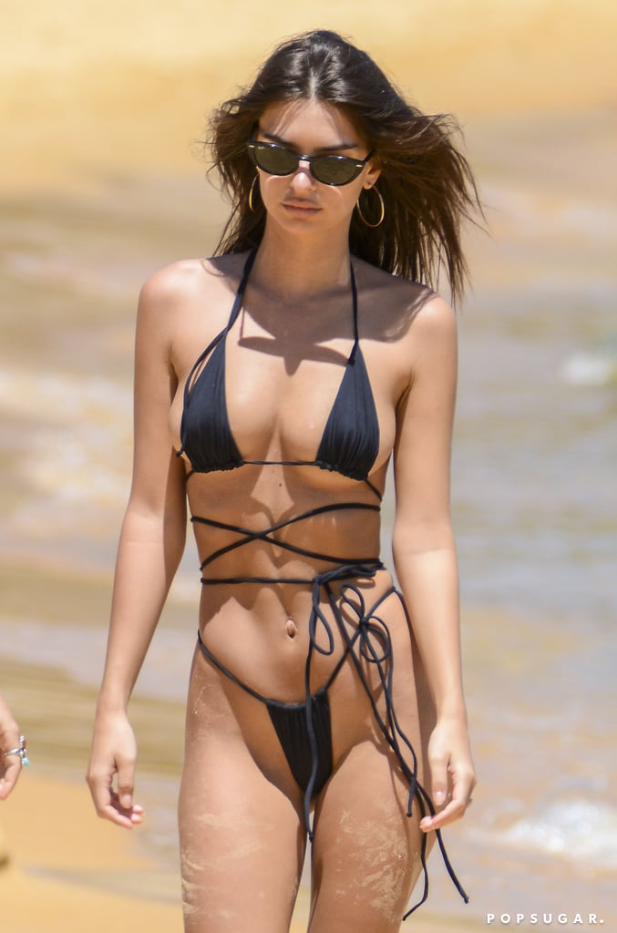 """While most of us are cozying up in jeans and sweaters, Emily Ratajkowski has found a smart way to ensure Summer never ends . . . by heading to Australia, where the warm weather is only just beginning. And who can blame her? This is a woman who was born to hit the beach. Emily is definitely no stranger to sexy swimwear — she's basically a professional bikini wearer by this point — but this week, she hit the beach in Sydney wearing one of her most memorable designs yet. If you were thinking """"this bikini is made for her,"""" you're absolutely right: it's part of her own swimwear collection, like so many other suits she's worn this year. Emily wore the black strappy, high-cut design gathered tightly to show as much skin as possible. Paddling in the ocean with a friend, she showed off the body that's landed her campaigns with the likes of DKNY and Paco Rabanne. Keep reading to take a closer look for yourself."""