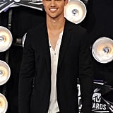 Taylor Lautner wore a blazer over a buttoned shirt.