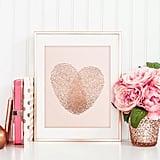 بصمتا إصبع على شكل قلب بلون الذهب الورديّ المعدنيّ والزهريّ الفاتح في الخلفيّة (بسعر 10$ دولار أمريكيّ؛ 48 درهم إماراتيّ/ريال سعوديّ)