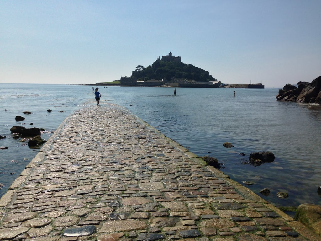Unlike other islands, St. Michael's Mount can be reached in two ways: by boat or by foot. The medieval church and castle in Cornwall, England, features a man-made causeway that visitors can walk across from Marazion Beach — but only during mid or low tides. At high tides (during Spring, Summer, and Fall), the cobbled walkway is covered by the ocean and passage is only possible by boat.   The St. Aubyn family and a small community of islanders inhabit the Mount, but its long history dates far back to familiar myths and legends. Tales that originated in 495 AD say mermaids lured ships to the rocks or that archangel St. Michael guided them to safety. Pilgrims, monks, and others guided by faith have come to the island since to pray and celebrate. In addition to being a spiritual landmark, St. Michael's Mount is also said to be lucky for love. It is believed that those who touch the highest point of the bedrock will be granted a romantic wish, especially before a proposal or wedding. The popular legend of Jack the Giant-Killer also originated on the island, where Cormoran the giant was said to have lived. A young man named Jack from Marazion supposedly walked across the causeway to slay him.  In 1066, the monks of Mont Saint-Michel in Normandy, France, took over the castle and built the church and monastery that still stand today. Watch a time-lapse video that shows the change of tides, and see the amazing photos after!      Related:                                                                                                           This Ancient Greek Wonder Looks Like Mystical Floating Cliffs