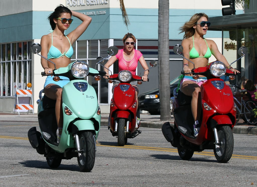 The St. Petersburg, FL, set of Spring Breakers got an extra dose of fun when Selena Gomez and Vanessa Hudgens filmed a scene on Vespas this afternoon. Selena was in a bright bikini while Vanessa wore a neon green two-piece. Their costar Ashley Benson joined them for the ride in her own pink suit. The ladies have been hard at work on the movie for the last two weeks, though Selena has been able to break from the cameras to spend time with boyfriend Justin Bieber. She traveled back to LA to celebrate his 18th birthday earlier this month and got a visit from Justin on location over the weekend. The couple went fishing with friends and Justin showed off his new ankle tattoo, which depicts praying hands.