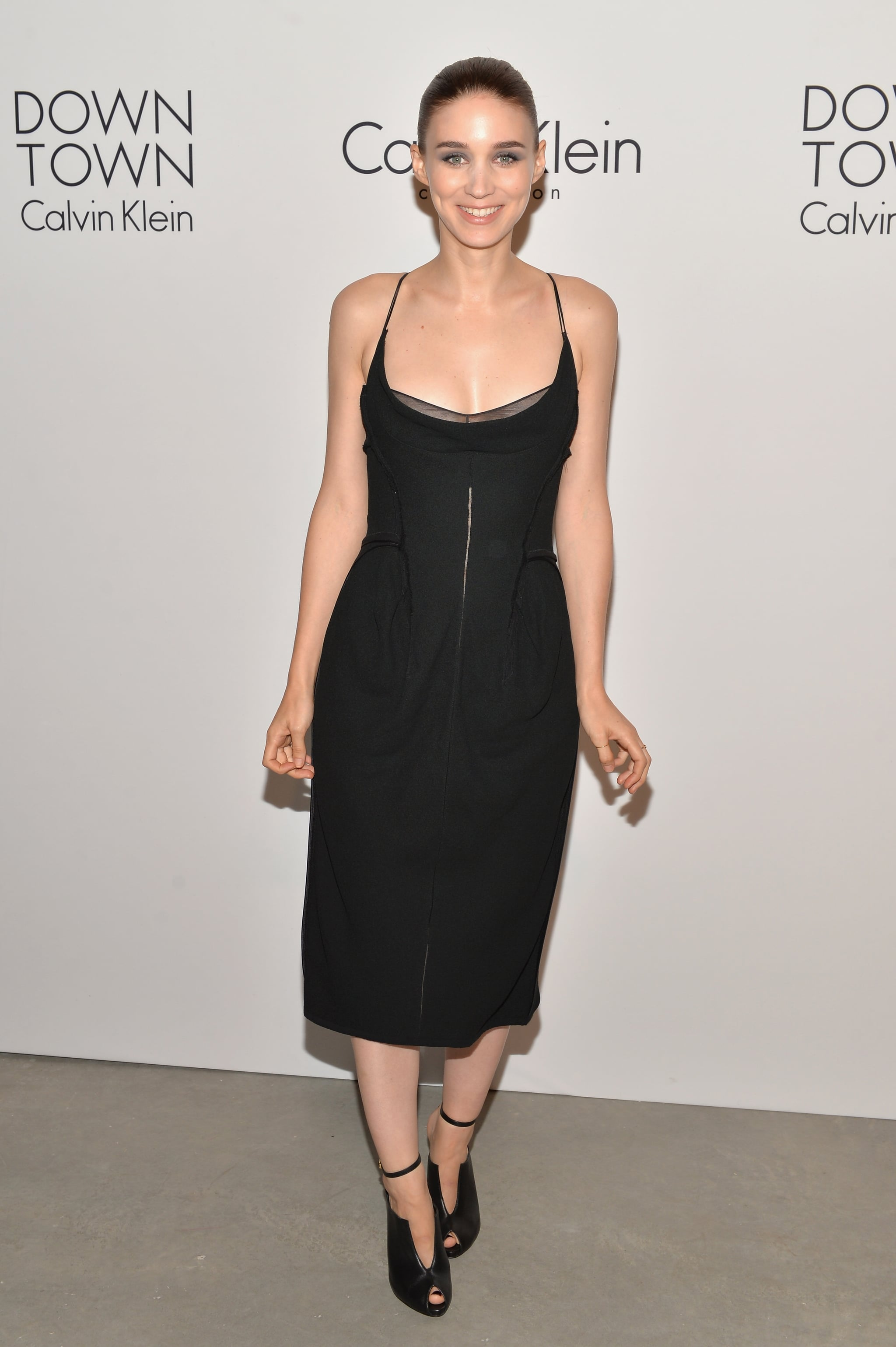 Rooney Mara dressed in a black midi dress and peep-toe booties at the Calvin Klein Collection afterparty.