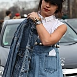 Miroslava Duma completed her all denim Chanel look with black cap, black and white clutch, and stacked jewels.