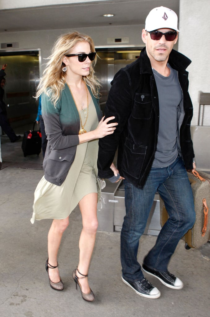 LeAnn Rimes and Eddie Cibrian held hands departing LAX today. The pair spent the night in Houston after LeAnn belted out the National Anthem at the NCAA basketball championship game. She took to the court in a white Dolce & Gabbana minidress, though her performance was overshadowed by people commenting on her slender frame. LeAnn took to her Twitter account last night and today to address the concerns, but mostly to tell people to mind their own business.