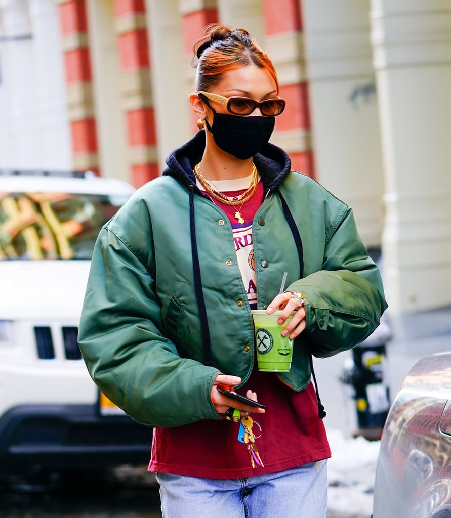 Bella Hadid is bidding farewell to 2020 with arguably the coolest hair trend of the year: chunky highlights. On Tuesday, the model was spotted in New York City sporting new face-framing orange highlights tucked into her signature sleek updo. Chunky highlights made a huge comeback earlier this year, and Hadid joins celebrities like Dua Lipa, Jennifer Lopez, and Kylie Jenner who've previously rocked the nostalgic trend — which, by the way, isn't going anywhere in 2021. Upon further investigation (aka stalking Hadid's Instagram Stories), it looks like the model's fresh colour is the work of celebrity hairstylist Evanie Frausto, who's also responsible for many of Hadid's '90s-inspired 'dos. She shared a glimpse of the dye process on her Instagram Monday, and debuted the finished look the following day. Hadid most recently played around with another very trendy style — the shag haircut — so it's no surprise the model changed up her look once again. Ahead, take a closer look at Hadid's latest cool-girl hair transformation.
