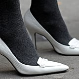 White pumps were paired with gray tights for a weather-appropriate take on one of the season's hottest trends.