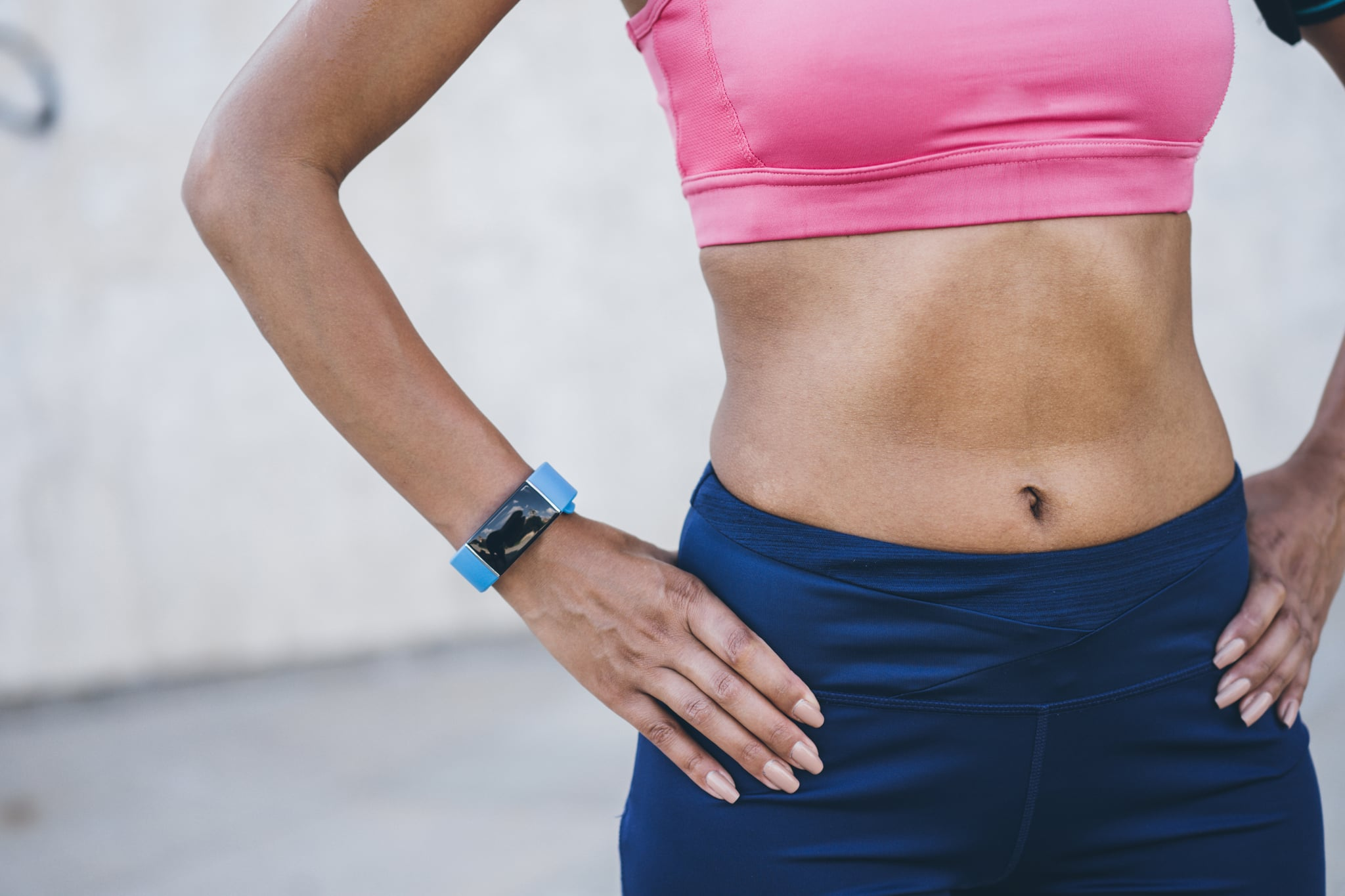 Female athlete with her hands on hips wearing smart watch