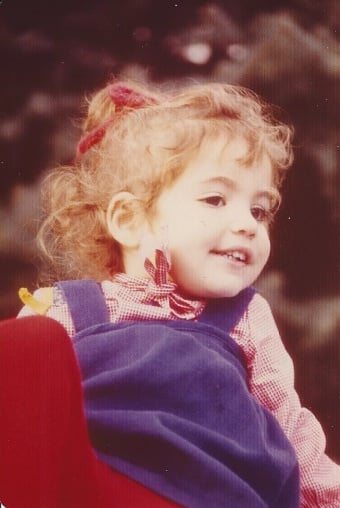 """Seventies style certainly gives us something to laugh at today! I'm about 3 years old in this picture and playing in my cousins' backyard. The yarn bow in my hair was definitely my signature style as a tot! —  Rebecca Gruber, editor, POPSUGAR Moms"