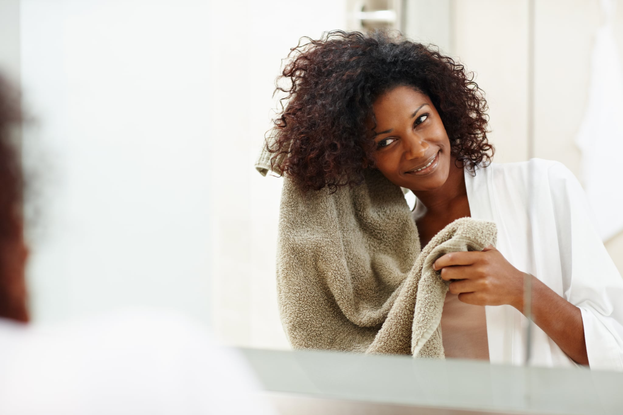 Beautiful african woman drying her hair with a towel in the mirror