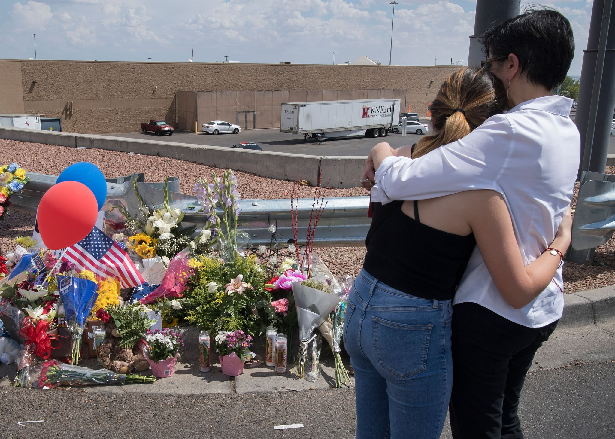 People hug beside a makeshift memorial outside the Cielo Vista Mall Wal-Mart (background) where a shooting left 20 people dead in El Paso, Texas, on August 4, 2019. - Texas authorities are investigating the Saturday mass shooting at a Walmart store in El Paso as a possible hate crime, the city's police chief said, as authorities study an online manifesto linked to the suspect. A 21-year-old from Allen, a suburb of Dallas, surrendered to police outside the store after the rampage that left 20 people dead and 26 wounded.US media identified him as Patrick Crusius, who is white, and linked him to a