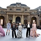 "Camila standing on the ""Le Defile L'Oreal Paris"" fashion show stage beside (from right to left) Aishwarya Rai, a L'Oréal model, Helen Mirren, Amber Heard, Doutzen Kroes, and Liya Kebede."