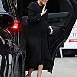 She teamed the coat with a black pleated skirt with an asymmetrical hemline, and beige pumps.