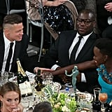 Brad Pitt chatted up Lupita Nyong'o and Steve McQueen at their table.
