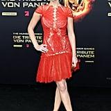 تقدّمت جينيفر لورنس لحضور العرض الأول في برلين لفيلم ذا هانغر غيمز بفستان ماركيزا جذّاب، وحذاء أحمر بكعب عال من جوسيبي زانوتي ليتسق مع الفستان، ومحفظة ذهبية من فيراغامو بيدها، لتحقيق التوازن المثالي بين الأنوثة والجاذبية.