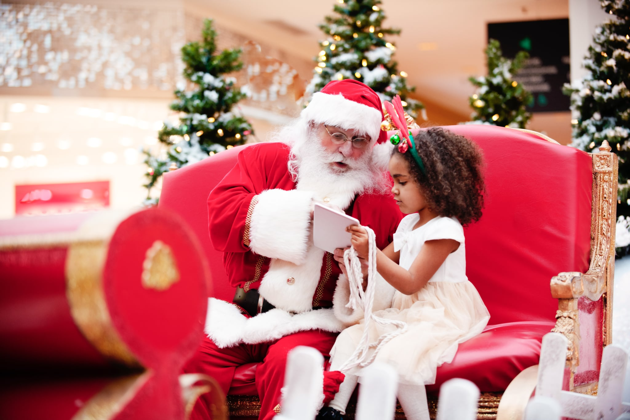 Multi-Ethnic family shops at Shopping Mall during Christmas Time with Santa Claus. Santa Claus and girl are shopping with digital tablet. Santa and girl is looking at the digital tablet. Santa Claus has a beautiful expression on his face. Photo was taken in Quebec Canada.