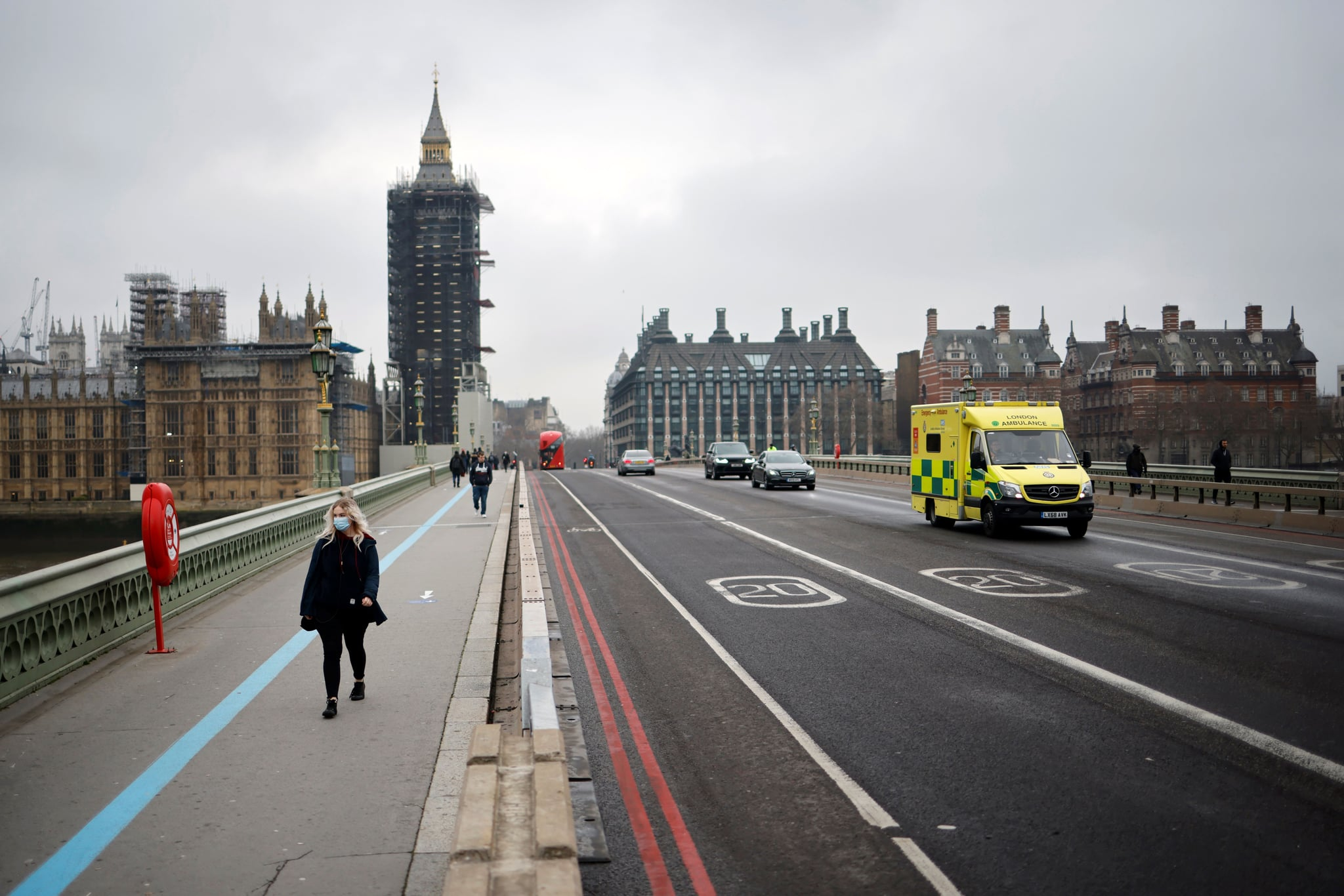 A pedestrian wearing a face mask walks across Westminster bridge as an ambulance passes by in central London on January 8, 2021, as England entered a third lockdown due to the novel coronavirus Covid-19. - Faced by a sharp rise in coronavirus infections, driven by the new strain, England entered a strict lockdown on January 5, 2021, with schools and non-essential shops closed for at least six weeks after previous measures failed to halt the steep rise in cases. (Photo by Tolga Akmen / AFP) (Photo by TOLGA AKMEN/AFP via Getty Images)