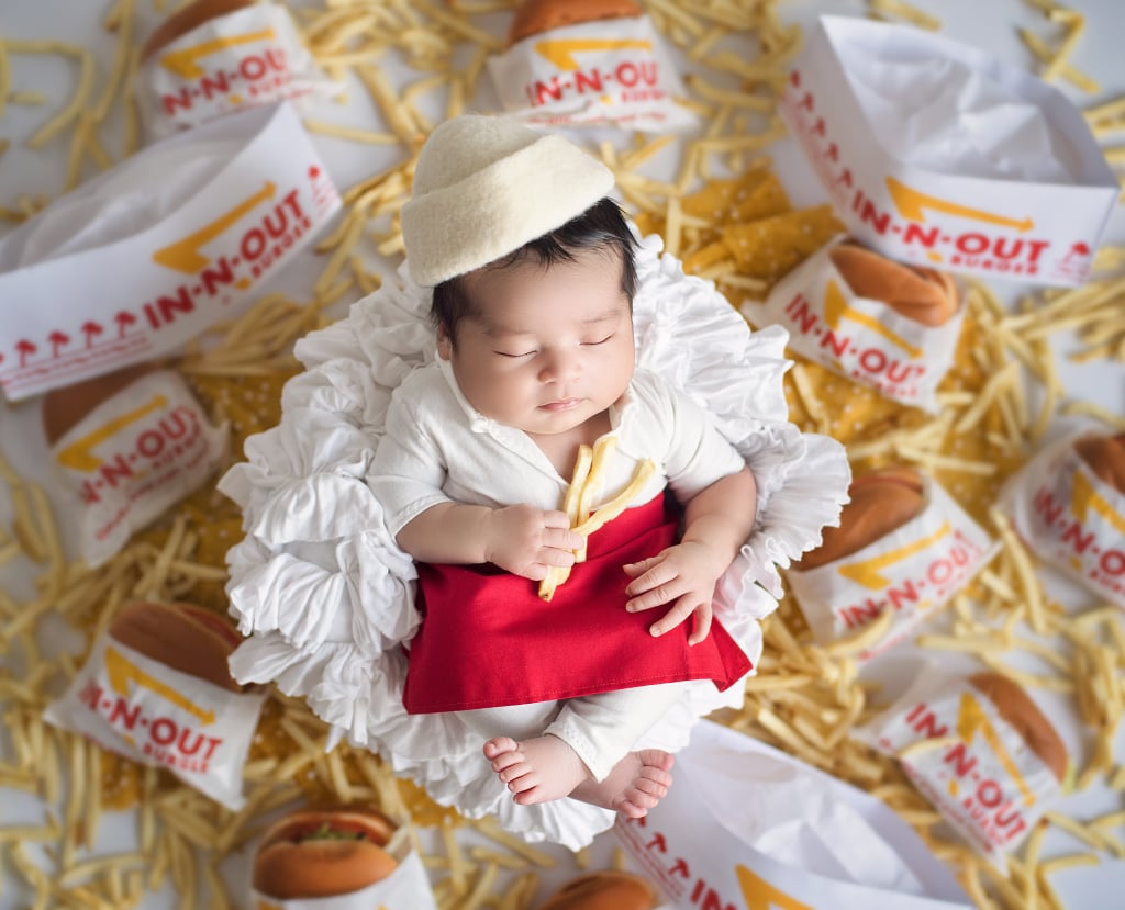 "Karen Marie, the photographer behind Belly Beautiful Portraits, who is known for her wide array of photo shoot themes — like newborns dressed as Disney princesses and Disney villains! — has officially made her foray into fast food. Karen shared the results of a recent newborn photo shoot with an In-N-Out Burger theme on Instagram, and it's beyond hunger-inducing.  ""At a studio consultation, my clients told me they met while working at In-N-Out, and immediately, my creative wheels started to turn!"" Karen told POPSUGAR. ""I consulted with my prop vendors, and they came home with the outfit and hat. I'm currently in the prep phase for a fitness competition, and once in a while I crave a burger, so it was hard to go get 20 burgers and fries and smell it while shooting. Still, it was well worth the results! The parents are in love with the photos, and I can't wait until after my competition to eat a few fries."" Read ahead to get a peek at Karen's latest delicious work. And FYI: we're not responsible for the animal-style French fries cravings you might have afterwards!      Related:                                                                                                           These Newborns Got Down With Their Bad Selves in a Gorgeous Disney Villain Shoot"
