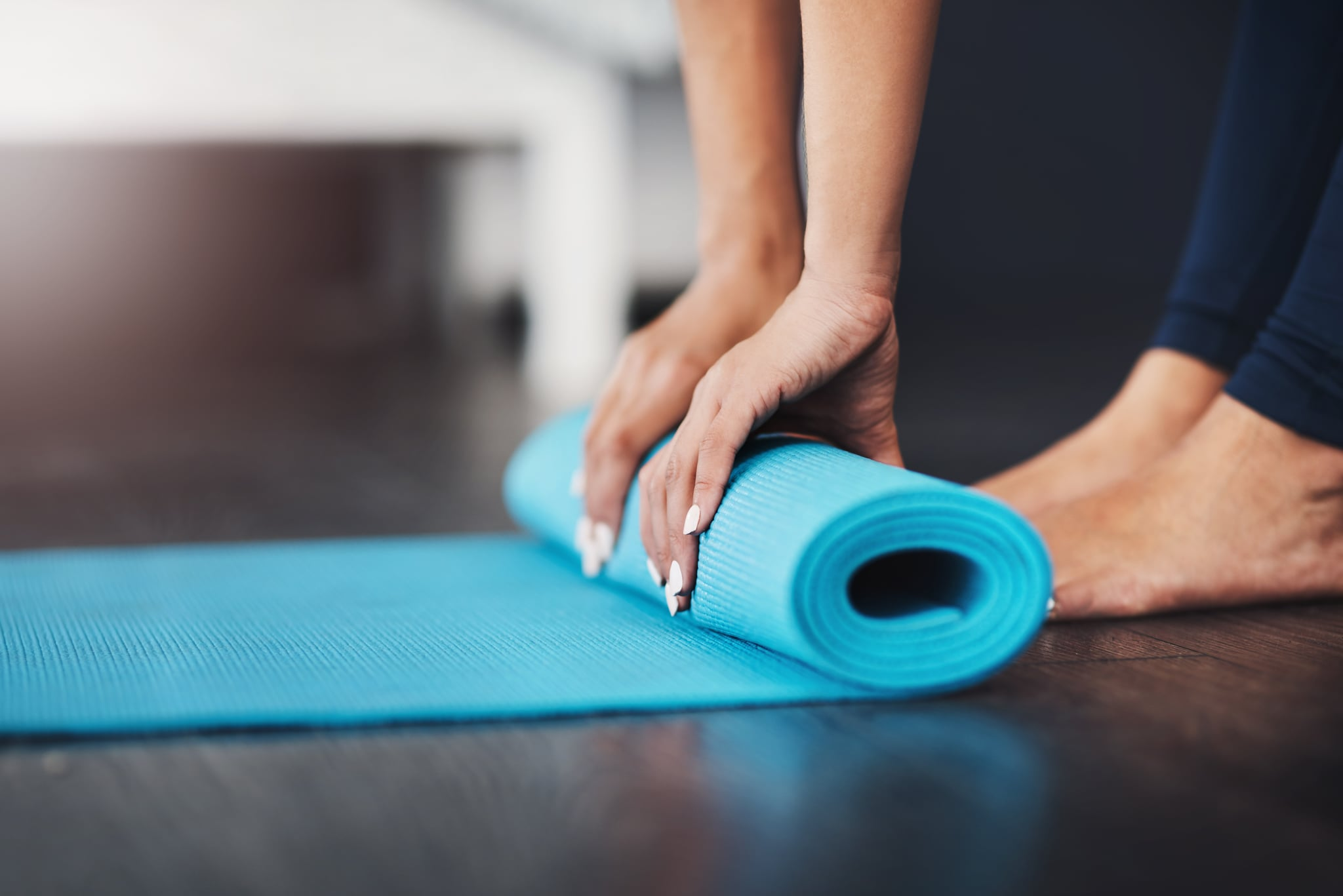 Cropped shot of an unrecognisable young woman rolling up her yoga mat in her bedroom
