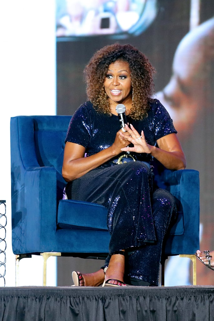 Michelle Obama has been crushing her wardrobe game while promoting her memoir, Becoming. She has been seen wearing everything from an embellished light pink suit to a pair of Alexander Wang leather pants. Most recently, Michelle was seen giving a talk during the 2019 Essence Festival, which took place at the Louisiana Superdome in New Orleans.  The former FLOTUS wore a custom Sergio Hudson creation that just about took our breath away. Rather than wearing a suit or an LBD, Michelle decided to have some fun in a sequinned midnight blue jumpsuit. The one-of-a-kind creation had a '70s feel with its wide-leg silhouette. She accessorised with a matching silk satin belt that cinched in her waist, also by the designer. To complete her outfit, Michelle slipped into a pair of strappy heels that came in a similar hue. This actually isn't the first time she's worn a head-turning jumpsuit this year. She previously chose a custom black embellished Stella McCartney jumpsuit while promoting her memoir in London. Clearly, she knows how to rock the heck out of the style!  Keep reading to see her amazing sequinned jumpsuit from all angles. Then, shop similar versions if you also want to give her sparkly look a try.       Related:                                                                                                           Anyone Can Wear a Summer Dress With Sneakers, but Michelle Obama Is the Master