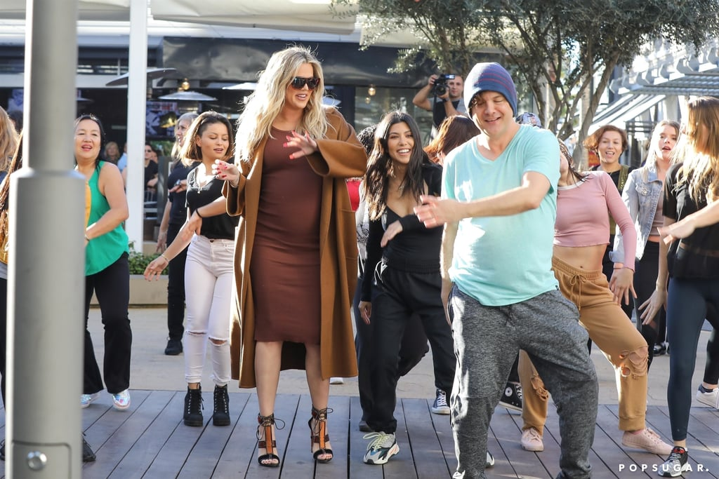"""When it comes to the Kardashian-Jenner clan, Kim Kardashian definitely likes to be the cooler one of the bunch. She sets fashion trends, she's the master of highlighting and countouring, and she even claims to have invented the selfie, but the one thing Kim doesn't do is dance. On Thursday, Kourtney and Khloé surprised Kim with a flash mob at the Topanga Mall near LA while filming an episode of Keeping Up With the Kardashians, and naturally, Kim's reaction was priceless. Not only was she totally """"confused"""" about what was going on, but instead of joining in, Kim stood off to the side and watched in amusement.  Still, that didn't keep Kourtney or Khloé, who is currently six months into her pregnancy, from joining in. Kim later tweeted about the entire thing, writing, """"OMG you guys!!!! I just experienced a flash mob!!!! @kourtneykardash @khloekardashian & @ForeverKhadijah surprised me with a flash mob in the middle of the mall!"""" Honestly, it looked like a blast!  OMG you guys!!!! I just experienced a flash mob!!!! @kourtneykardash @khloekardashian & @ForeverKhadijah surprised me with a flash mob in the middle of the mall! — Kim Kardashian West (@KimKardashian) January 12, 2018   And yes they were dancing in the flash mob! I was dying!!!! Like literally crying laughing and confused all at the same time. It was amazing! — Kim Kardashian West (@KimKardashian) January 12, 2018"""