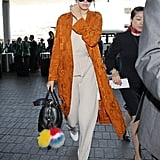 When it comes to jet-setting, Kendall Jenner knows to pack the chicest top layer there is: a bright-colored duster!