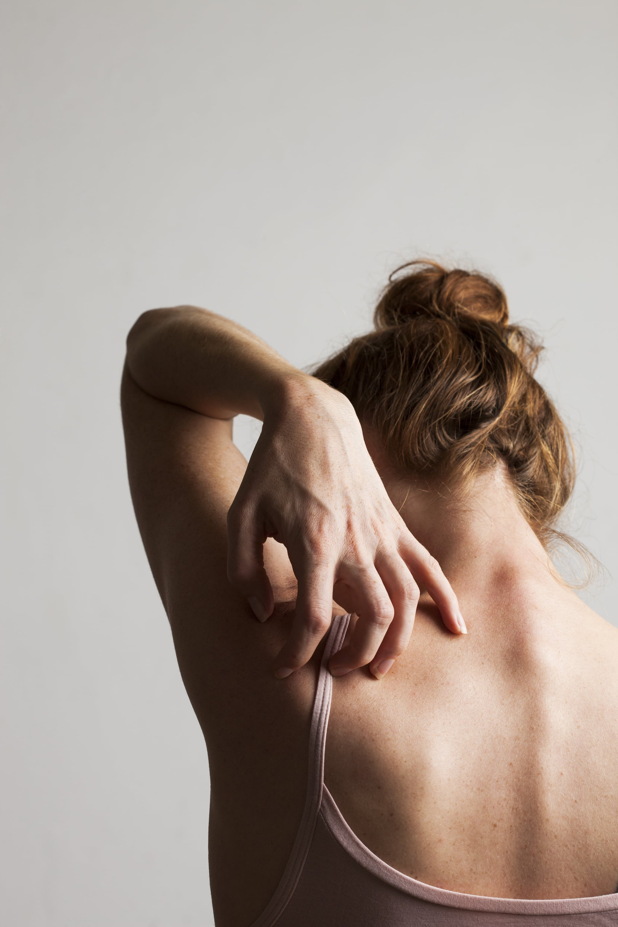 MODEL RELEASED. Woman scratching her itchy back.