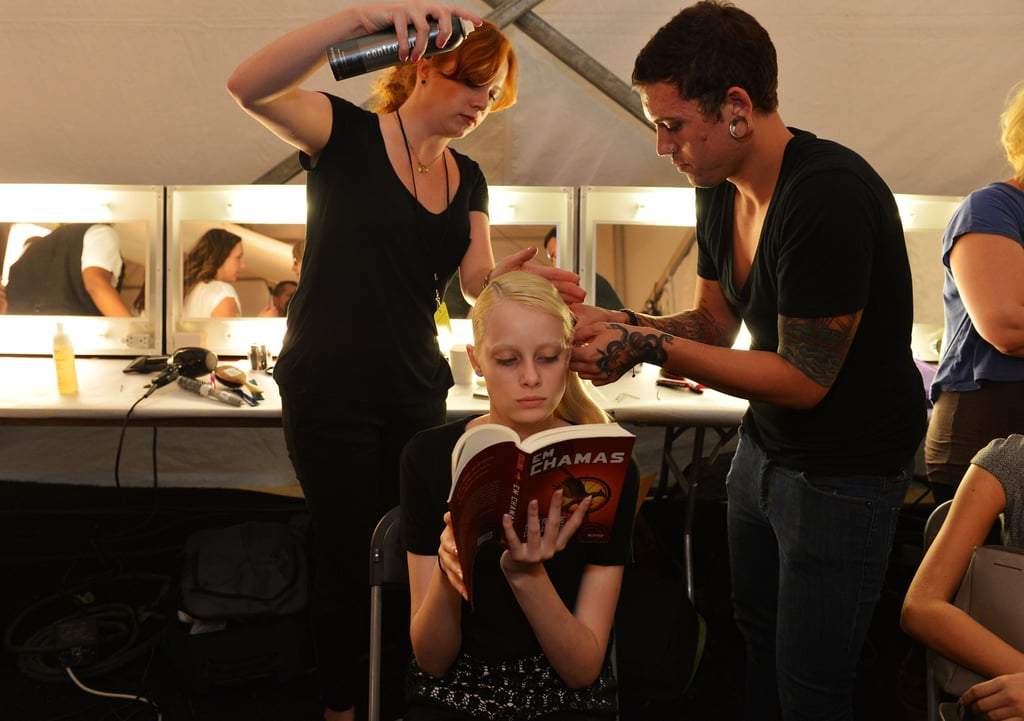 This model got her hair done backstage while she read the Portuguese version of Suzanne Collins's second Hunger Games book, Catching Fire (Em Chamas).