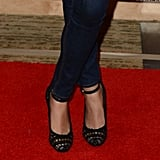 A close-up of Mila's open-weave ankle-strap heels.
