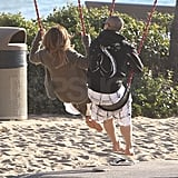 Jennifer Lopez and Casper Smart played on a swing set.