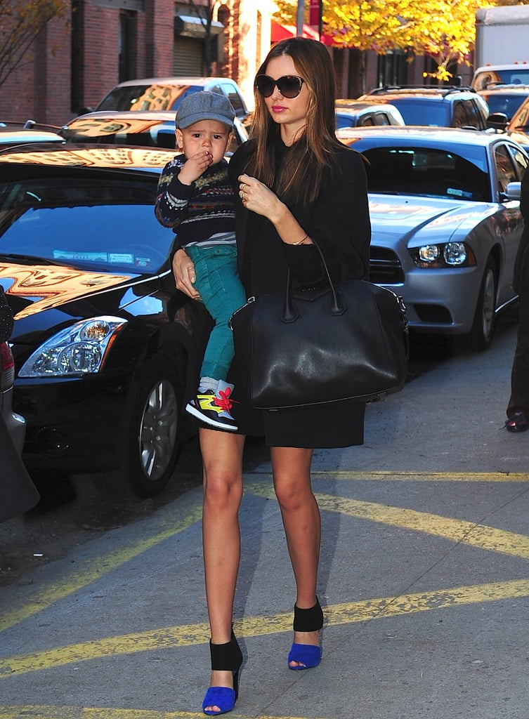 This is how to perfectly pull off an all-black look. Miranda varied the textures of her coat, dress, and Givenchy tote to add visual interest while adding an unexpected pop of blue with a pair of Pierre Hardy sandals — though her best accessory is obviously the adorable Flynn.