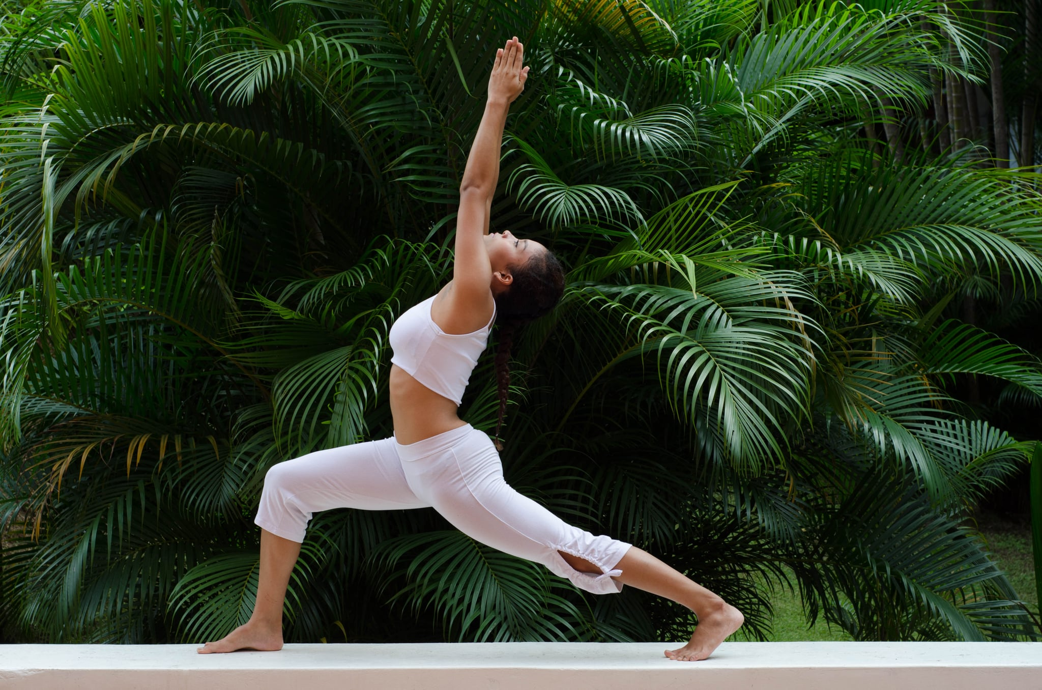A woman doing a yoga pose on a garden (Ashwa Sanchalanasana)