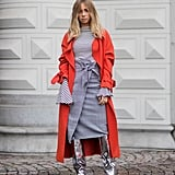 Top off your stripes with a checked wrap skirt in shades of gray, then throw on a pair of statement boots and some bright outerwear.