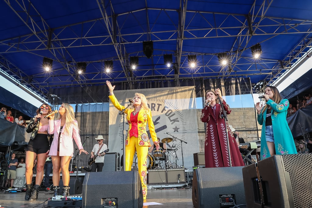 """Dolly Parton decided to stop by the Newport Folk Festival in Rhode Island for a good time on Saturday! The singer surprised attendees by uniting on stage with country music group The Highwomen — which consists of singers Brandi Carlile, Natalie Hemby, Maren Morris, and Amanda Shires — as well as Sheryl Crow, Lucy Dacus, and Maggie Rogers. Sporting an embellished yellow floral suit with a red bustier, Parton belted a handful of her classics, notably her 1974 hit """"Jolene"""" and 1980 tune """"9 to 5."""" After the show, Parton took to Instagram to share her excitement over the special appearance. """"I just love surprises! You should have seen the look on your faces,"""" she captioned the post. """"Thanks for having me."""" Carlile also gave the famous country crooner a shout-out, posting a photo of the two embracing on stage. """"Dolly. I will always love you. And I will never forget today,"""" she wrote, referencing Parton's 1974 hit """"I Will Always Love You."""" Keep scrolling to view more videos and photos from the incredible stageing!"""