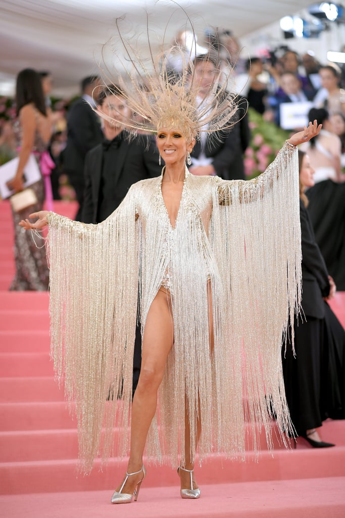 """When it comes to making an entrance at the 2019 Met Gala, Celine Dion most definitely knows what she's doing. During the most talked about night in fashion, Celine showed up to the red carpet in a stunning gold Oscar de la Renta gown that weighed over 22 pounds and custom Celine pumps. According to the brand, she was inspired by the ornate costumes of the Ziegfeld Follies productions in the 1930s, but even Celine admitted she didn't know what to make of the """"Camp"""" theme at first. During her red carpet interview, she confessed to being """"confused"""" by what this year's theme entails, and we don't blame her — but that headpiece speaks for itself. With thin, long feathers around the crown and draping fringes made from microcut beads coming from her dress, Celine's outfit is truly regal. Ahead, see photos of Celine's Met Gala look from all angles, and prepare to be wowed.      Related:                                                                                                           These Met Gala Looks Are Dramatic Enough to Entertain You For the Rest of the Year"""