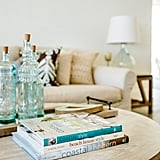 Decorative glass bottles, a rustic tray, wood pops, and a stack of gulf-coast-focused books create the perfect beach house coffee table.