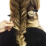 Let down the top half of your hair, reserving the sections on the left and right sides of your face for later use. Taking the strands from the crown of your head, create a french fishtail braid. Once you've plaited the whole section, pancake your finished braid to make it look softer. Not sure what a french fishtail is? This differs from a classic fishtail in that you will be adding a bit of the hair from the root each time you weave a segment of the style. For more instructions on how to create a french fishtail braid, go here.