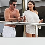 Shirtless Simon Cowell kept his sunglasses on while discussing trip details with friends.