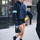 Have Prada, will travel. She toted it in June 2018 while rocking bike shorts, a fleece pullover, and Jimmy Choo boots.