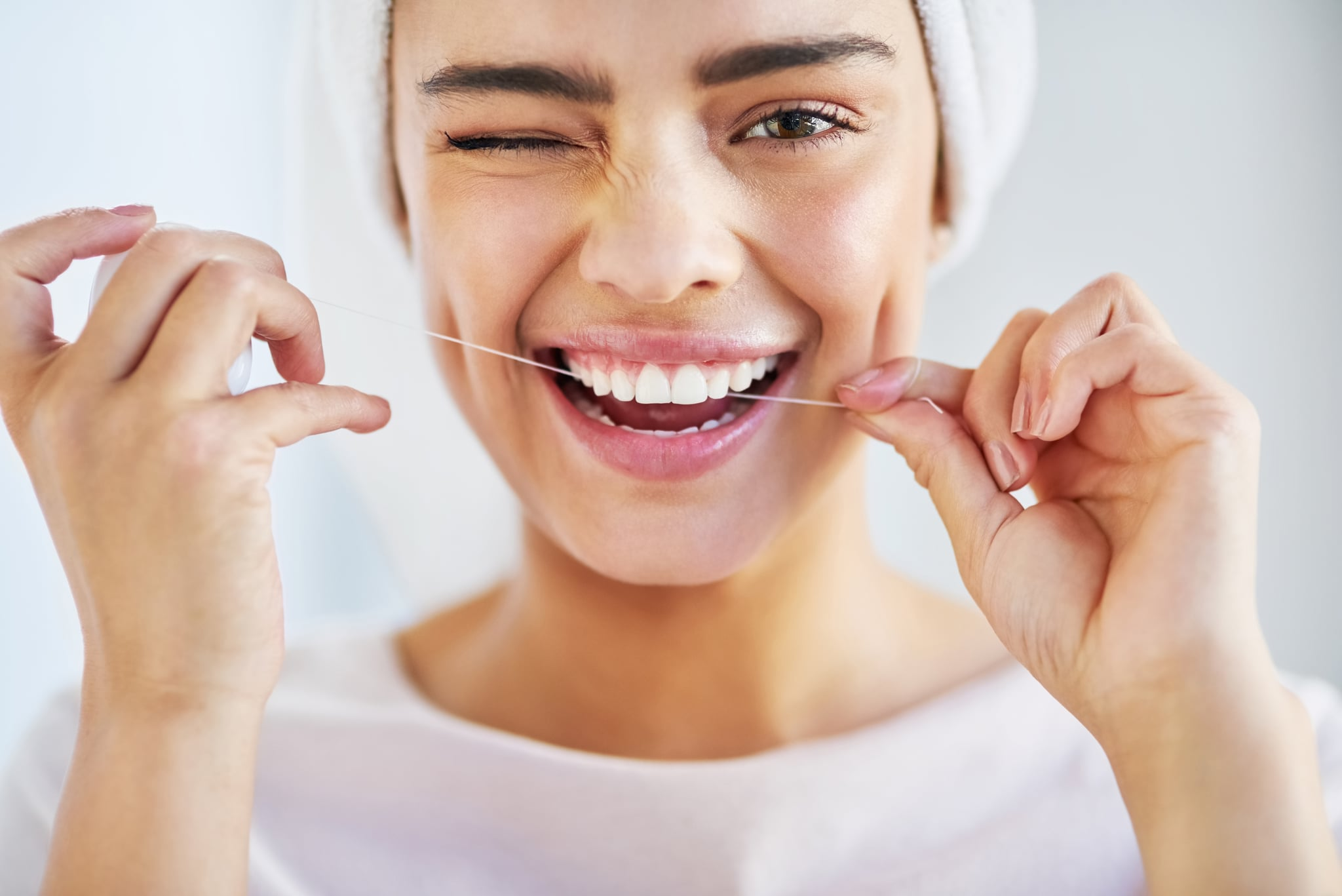 Portrait of a beautiful young woman flossing her teeth in the bathroom at home