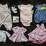 """Unworn baby clothes that were sitting in a bin in Abby's room. Many still had the tags on them."""