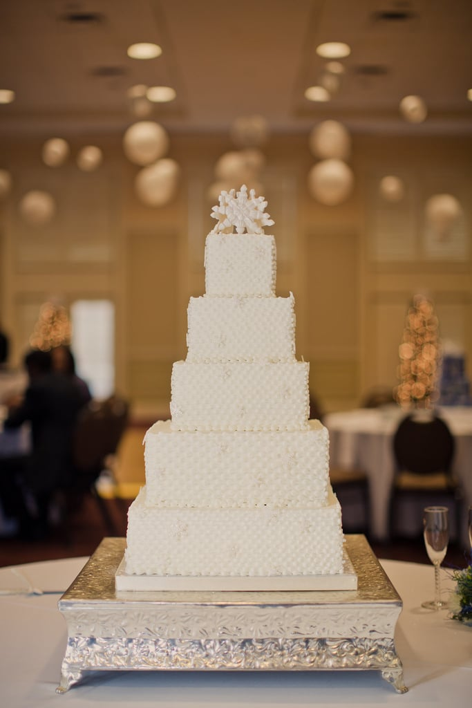 The details here are slight — piping, tiny snowflakes on all tiers, and two top snowflakes — making this cake effortlessly unique.