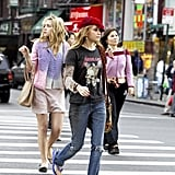 Roxy embraces the double-shirt trend from the early aughts in a Metallica tee, distressed denim, beret, and hobo bag. Jane, on the other hand, loves the ballet-flat trend and styles hers with a blazer and button-down.