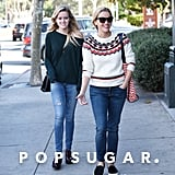 Reese wore skinny jeans with a Draper James sweater, and accessorized with the brand's printed Vanderbilt tote.